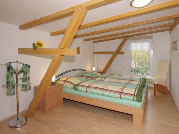 Schlafzimmer (1. OG) mit Doppelbett und genügend Platz für ein Kinderreisebett