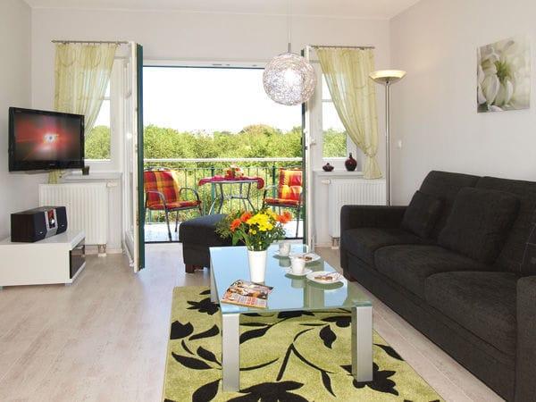 helles Appartement, Wohnbereich mit Zugang zum Balkon