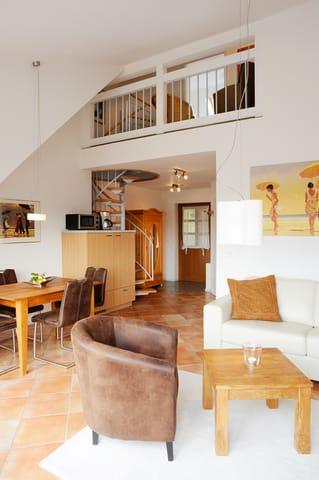 offener Wohnbereich mit Wendeltreppe in den oberen Schlafbereich