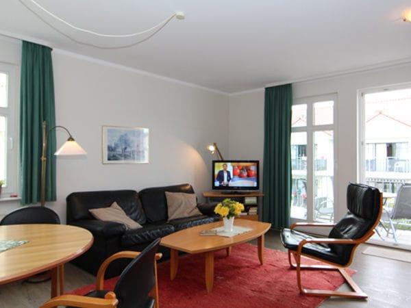 Wohnbereich mit Couch (Schlaffunktion für 1 Person) und Zugang zum Balkon