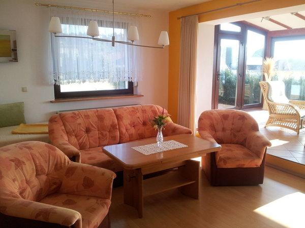 Wohnzimmer mit Übergang zum Wintergarten