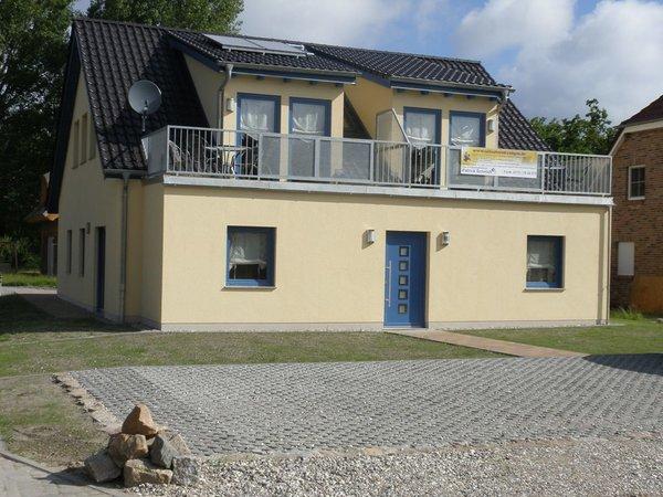 Hausansicht mit Balkon und Stellplätzen