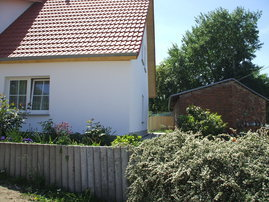 Seitenansicht des Hauses mit Blick aufs Wohnzimmerfenster der Ferienwohnung