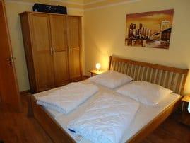 Schlafzimmer mit Doppelbett und 3-türigen Schrank