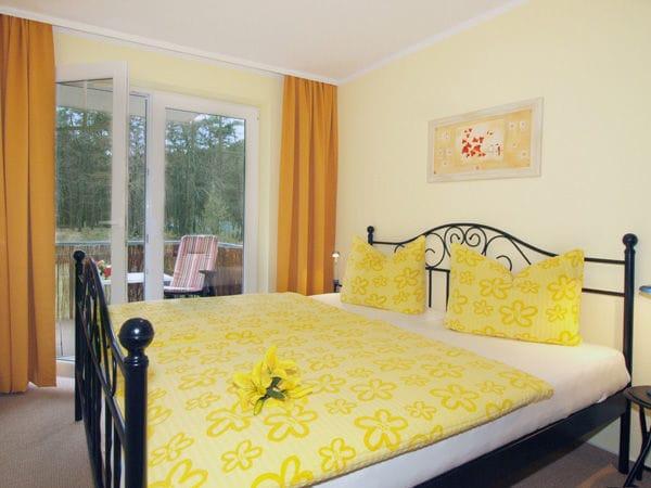 Schlafzimmer mit Doppelbett und Zugang zum Balkon