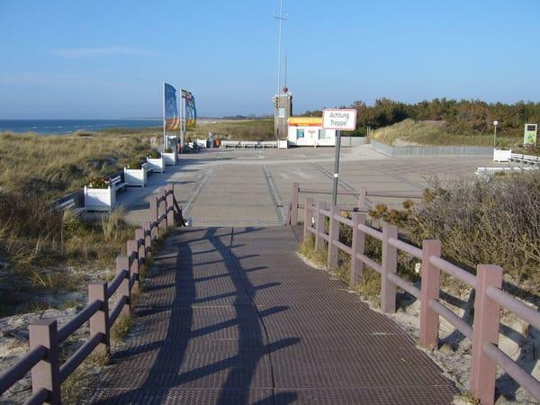 """Strandpromenade und """"Strandplateau"""" mit vielen Sitzbänken in der Sonne und Blick auf Strand und Ostsee. Im Hintergrund die DLRG-Wachstation."""