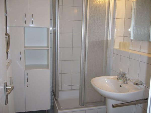 Geräumiges, weißes Duschbad mit Badezimmerschrank, Duschhandtuchstange, zahlreiche Haken und Ablagemöglichkeiten für Handtücher usw. Haltestange beim Duschausstieg.