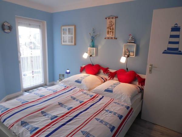 blaues Schlafzimmer in der unteren Etage mit komfortablem Doppelbett in 160 x 200 cm mit getrennten Matratzen, Kleiderschrank und kl. TV mit DVD sowie Zugang zur Terrasse