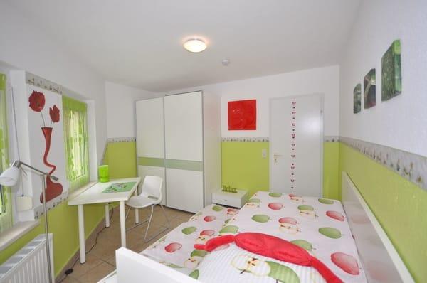 grünes Schlafzimmer in der unteren Etage mit 2 Einzelbetten (Etagenrollbett) je 90 x 200 cm, gr. Kleiderschrank und Schreibtisch sowie Zugang zur Terrasse
