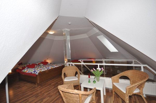 gemütlicher Schlafbereich in der Turmkuppel mit komfortablem Doppelbett in 180 x 200 cm mit getrennten Matratzen, einem kuscheligen Einzelbett in 90 x 200 cm, einer Sitzgruppe und dem kl. Balkon