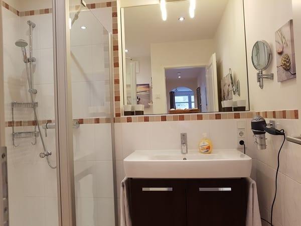 Im modernen Duschbad finden Sie einen Föhn, einen Vergrößerungsspiegel als auch einen Seifenspender vor.
