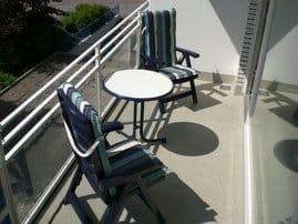 Süd-Balkon mit Tisch und Liegestühlen