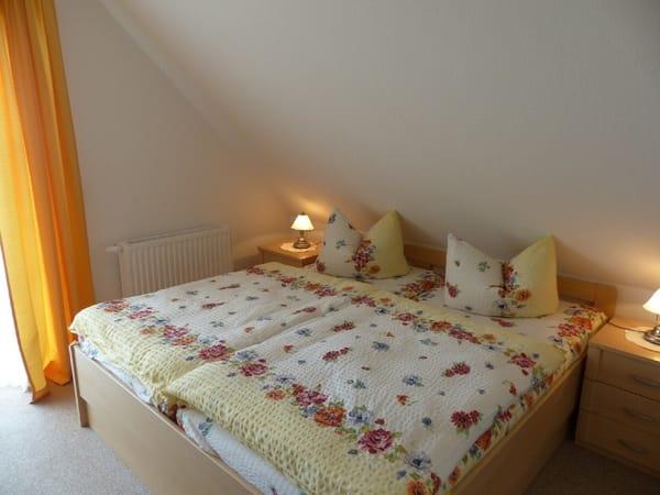 Eines der Schlafzimmer mit Doppelbett in konforthöhe Balkonwohnung