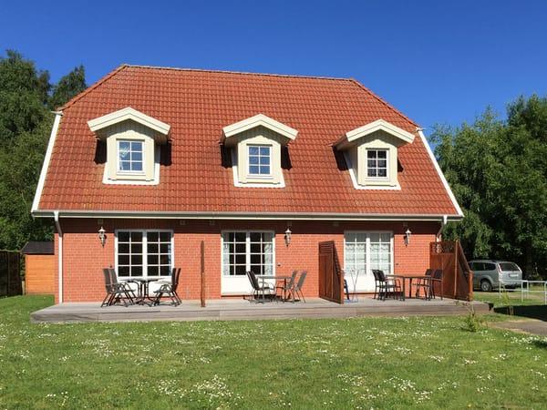 Ferienhaus Residenz zu den 3 Tannen Zingst - Aussenansicht rechter Reihenendhausteil mit Terrasse, Gartenmöbeln, großer Wiese und einer Schaukel für die kleinen Gäste