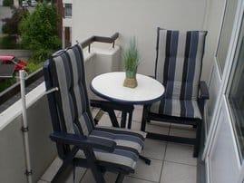 Balkon mit Tisch und Liegestühlen