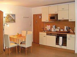 Wohnungseingangstür, Eßecke und Küchenzeile mit Geschirr