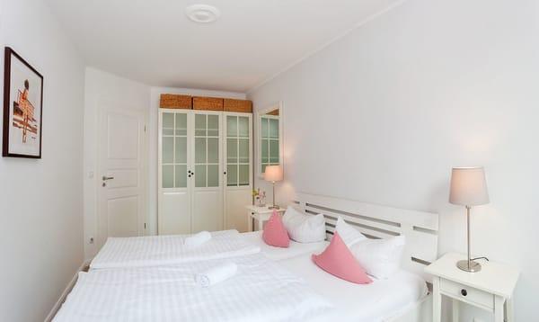 Das freundlich eingerichtete Schlafzimmer - mit komfortablem Doppelbett und Kleiderschrank ...