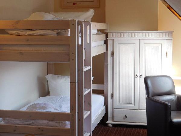 Im Dachzimmer stehen drei Betten bereit, genügend Spielraum bzw. gemütliche Rückzugsmöglichkeit mit Fernseher, WLAN und Büchern.