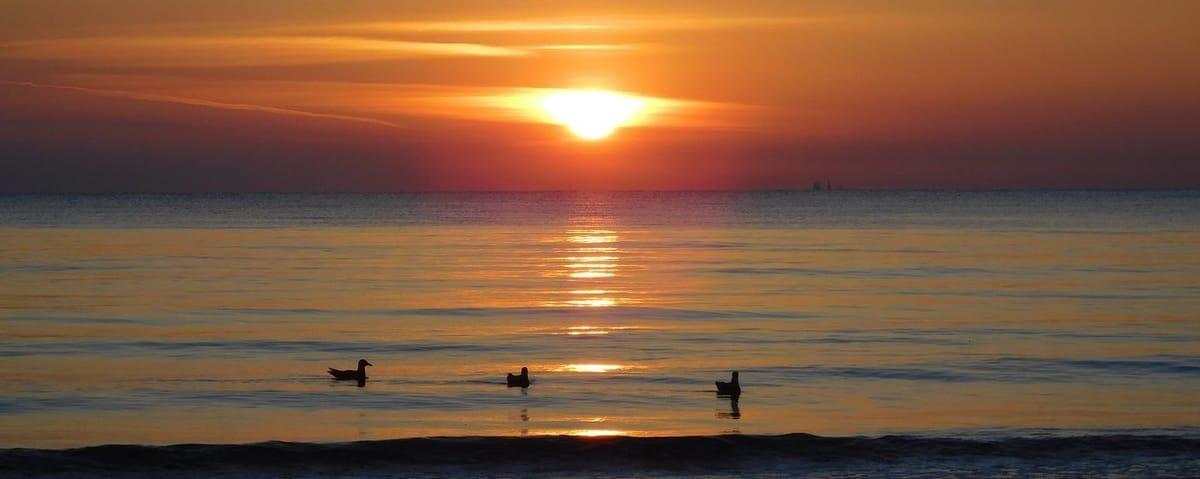 Sonnenaufgang am Strand. Der Feuerball scheint aus den Wolken zu fallen. Noch ist alles still
