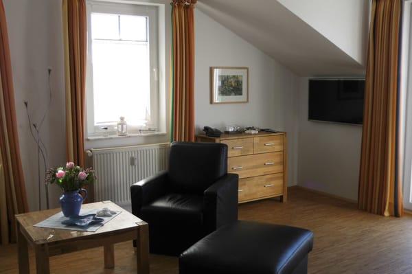... Sessel, Hocker und TV sowie Zugang zum Balkon