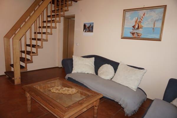 Wohnzimmer mit der Treppe zu den Schlafzimmern und der Toilette im Obergeschosss