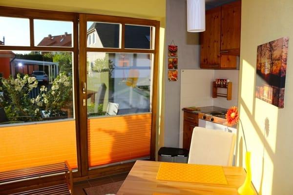 Der Blick von der Wohnküche geht hinaus auf die neue Gästeterrasse. Zur Wohnung gehören ein Terrassentisch und zwei Stühle.