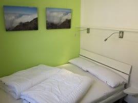 Separates Schlafzimmer mit Doppelbett, Kleinkinderausstattung bestehend aus Reisebett und Hochstuhl