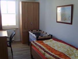 Separates Schlafzimmer mit Einzelbett, Schreibtisch und Schrank, Kinderreisebett