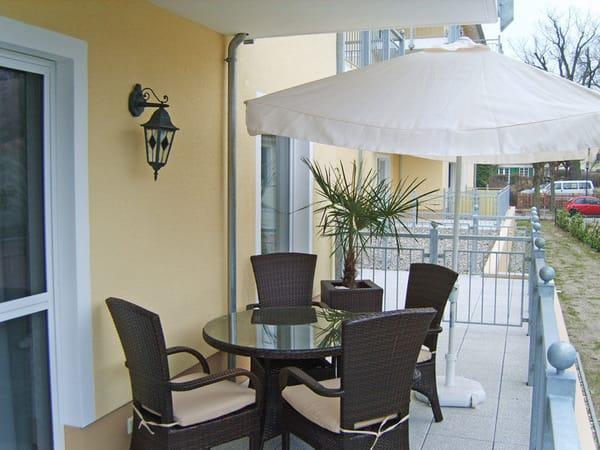Sitzecke auf der Terrasse mit großem Sonnenschirm und passender Sonnenliege