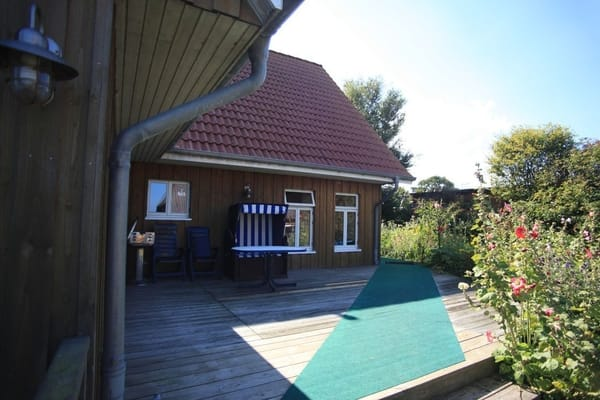 Holzterrasse mit Ostseeblick, Holzkohlegrill, Gartentisch mit 2 Gartenstühlen und einem Strandkorb.