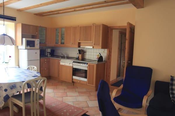 Küchenzeile mit Heißluftherd und Ceranfeld, Mikrowelle, Kühl-Gefrierkombination und Geschirrspüler. Außerdem Esstisch für 6 Personen mit Ostseeblick.