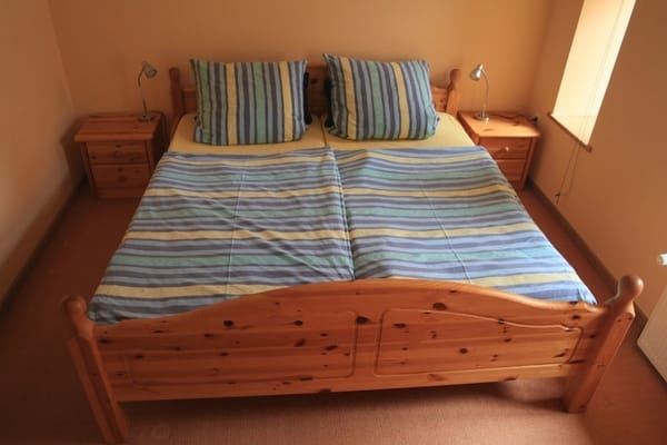 Schlafraum mit Doppelbett und Nachtschränken, 4-türiger Kleiderschrank und Stellplatz für ein Kinderbett