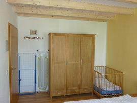 Schlafzimmer unten mit Kleinkinderbett.