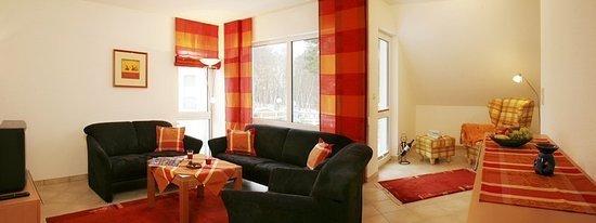 Wohnzimmer mit Leseecke und Zugang zum Balkon