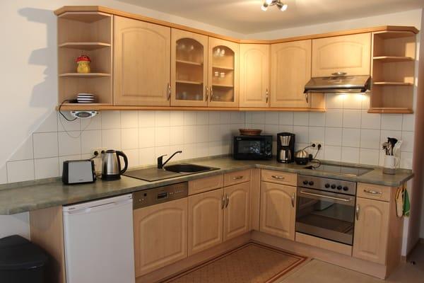 Moderne Küchenzeile mit Glaskeramikherd, Grill, Geschirrspüler, Mikrowelle, Wasser-/ Eierkocher, Kaffeemaschine, reichhaltige Geschirrausstattung