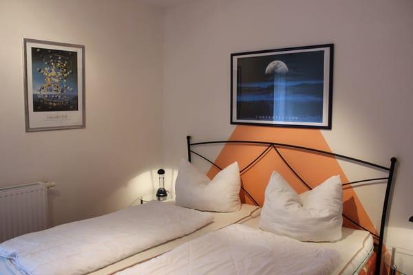 Schlafzimmer mit Doppelbett, Nachttischen, Leselampen und geräumigem Kleiderschrank