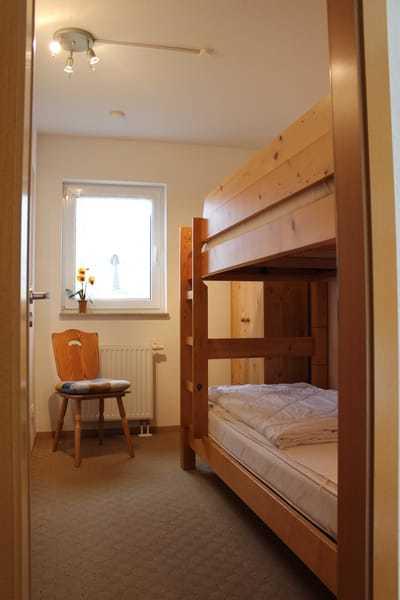Im kleinen Zimmer steht ein stabiles Etagenbett mit verstellbaren Lattenrosten, separate Leselampen, eine Kommode