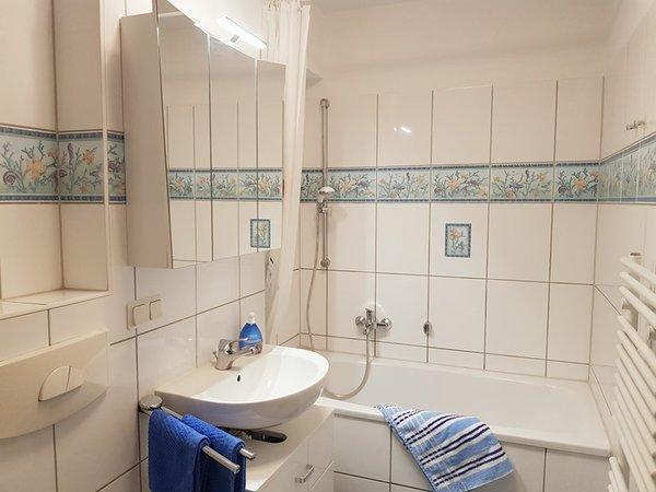 Maritimes Badezimmer mit Badewanne und Duscheinrichtung