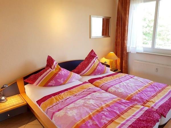 Schlafzimmer mit großem Fenster zum Küstenwald