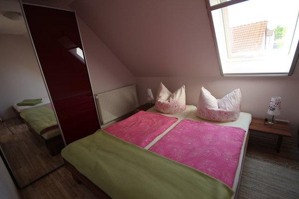 Im Schlafzimmer befinden sich drei Betten.