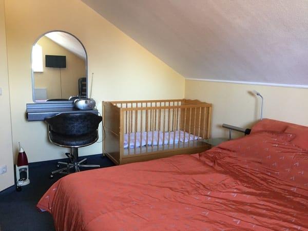 Schlafzimmer im Obergeschoss der Maisonette-Etagenwohnung mit Komfortbettanlage der Marke RUF, Kinderbett , großen Schiebetürenschrank und Schmink/Frisierplatz und einen 2. Fernseher an der Wand