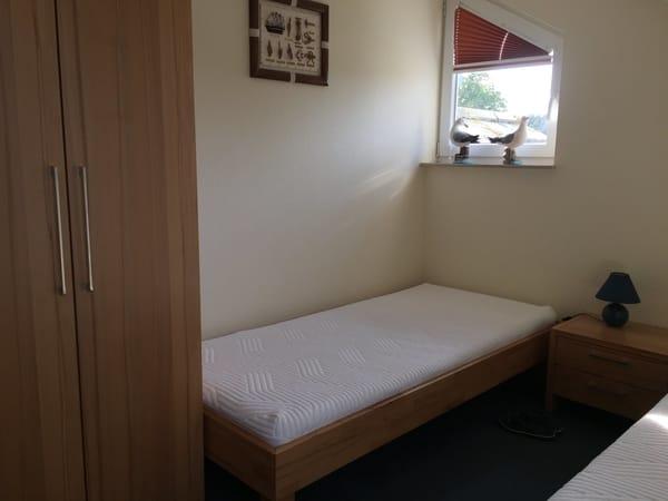 2. Schlafraum mit 2 Einzelbetten ebenfalls im Obergeschoss der Maisonette-Etagenwohnung, wo sich auch noch ein separates kleines Bad mit Toilette und Waschbecken sowie Platz für Utensilien befindet.