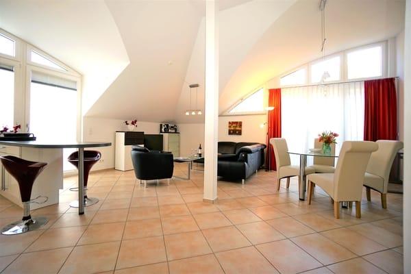 Geräumiges Wohnzimmer mit Esstisch und offener Küche