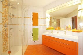 Im Badezimmer befindet sich eine ebenerdige, vollverglaste Regenwalddusche und ein Doppelwaschtisch.