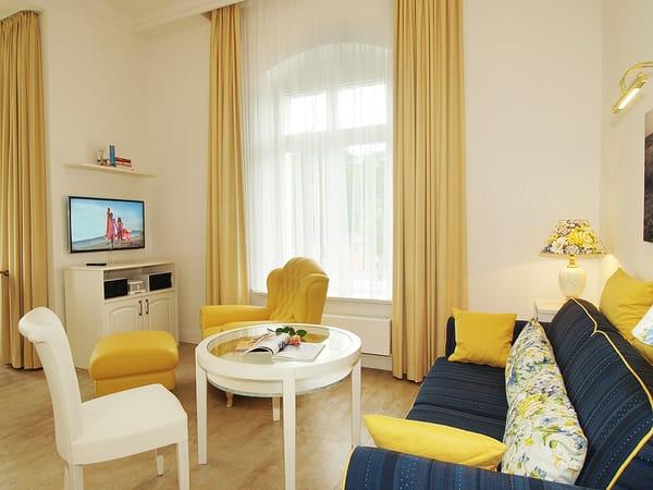 Der gemütliche Wohnbereich sorgt mit blau/gelben Farbakzenten für eine heitere Urlaubsstimmung. Modernste Technik wie Flat-TV, Internet-Anschluss, SONOS- Anlage und iPad versüßen Ihre Urlaub.