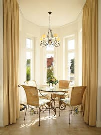 Im sonnendurfluteten Erker befindet sich die Essgelegenheit mit rundem Esstisch aus Glas und 4 äquivalenten Korbstühlen.