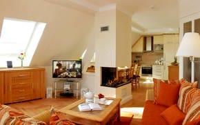 Im großzügigen Wohnbereich wartet eine gemütliche Sitzecke mit bequemen Polstermöbeln, Flat TV und Kamin zum Entspannen auf Sie.