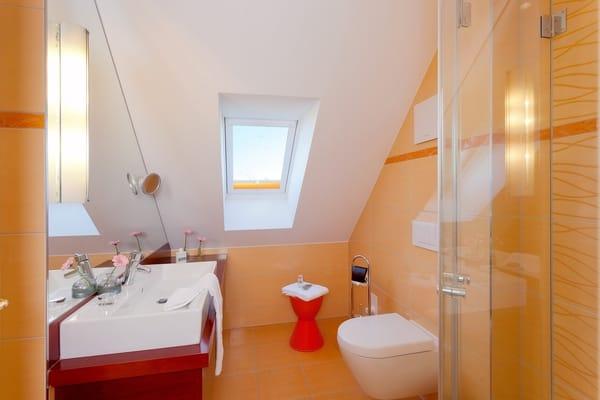 Das Badezimmer mit Fenster ist mit einer superflachen Duschtasse und einer Echtglas-Dusche, ...