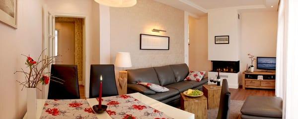 Der liebevoll eingerichtete Wohnbereich verfügt neben einer Relaxmöglichkeit auf dem edlen Ledersofa zusätzlich über einen Esstisch für 4 Personen.
