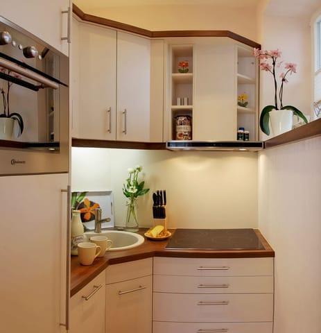 Die vom Wohnbereich optisch abgetrennte edle Küchenzeile ist mit allem ausgestattet, was Sie für die Zubereitung Ihrer Lieblingsspeisen benötigen.